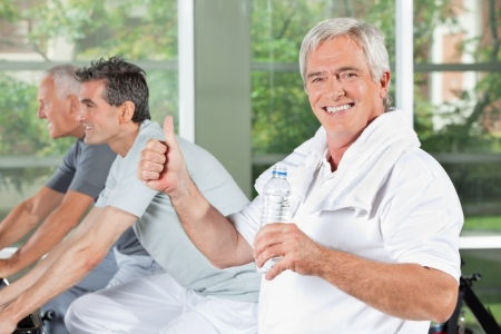 drink and drive: Happy senior man with water bottle in gym holding thumb up Stock Photo