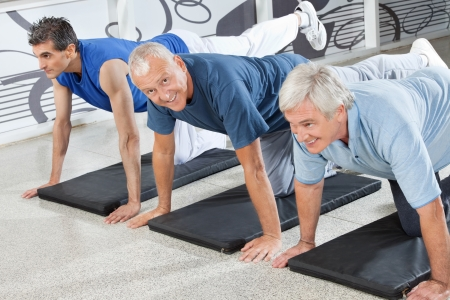 Three senior citizens training together in fitness center