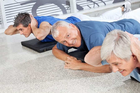 Happy senior man smiling on gym mat in fitness center Stock Photo - 12954067