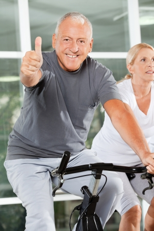 Happy senior man holding thumbs up on spinning bike in fitness center photo