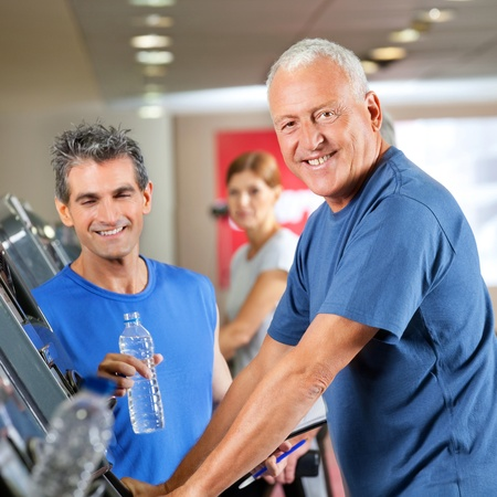 Happy senior man on treadmill with fitness trainer in gym photo