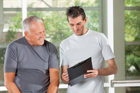 health club: Fitness trainer explaining training plan to senior man in gym