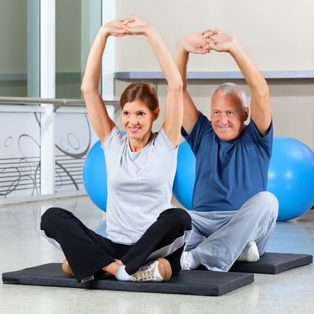 Elderly fitness group stretching their muscles on gym mats in fitness center photo