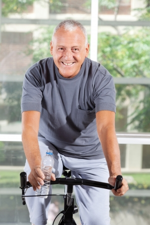 exercise machine: Happy senior man using a home trainer in a gym Stock Photo
