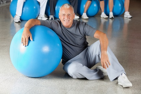 Happy senior man with gym ball in fitness center photo
