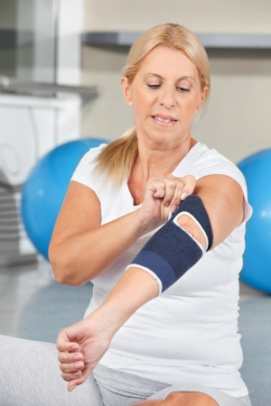elbow pain: Senior woman with bandage on elbow in fitness center