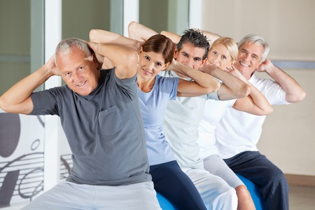 muscle formation: Happy senior people doing back exercises in gym
