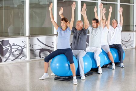 muscle formation: Gymnastics class for happy seniors on gym balls in fitness center Stock Photo
