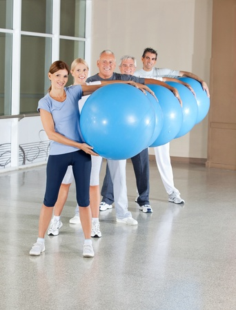 Senior people doing back training with gym balls in fitness center photo