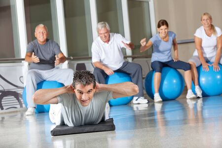 Man doing back exercises in gym with senior people around him