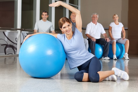 muscle formation: Happy woman doing back exercises with blue gym ball in fitness center Stock Photo