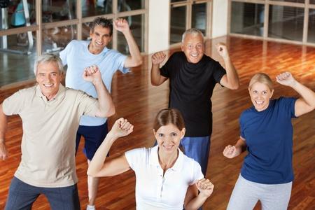 zumba: Feliz grupo de personas mayores en movimiento y el baile en el gimnasio