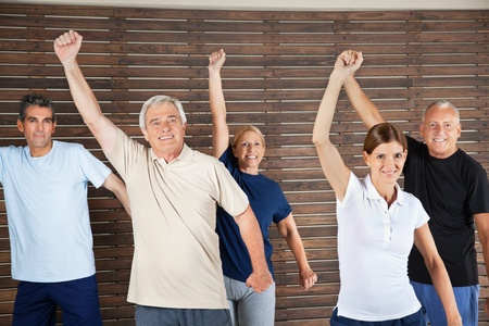 Happy senior citizens dancing to fitness music in gym