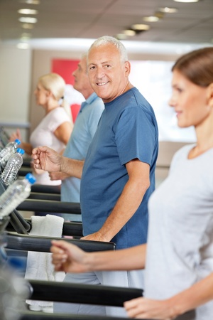 Senior citizens doing a treadmill training in fitness center Stock Photo - 12947787