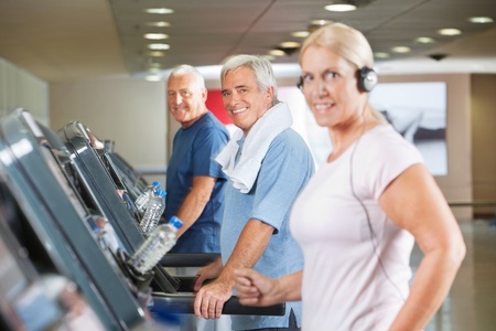 Happy senior group running on treadmills in gym photo