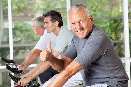 Happy senior man on bike holding thumbs up in fitness center photo