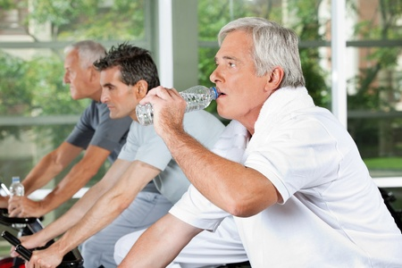 training device: Elderly man in fitness center drinking water from a plastic bottle