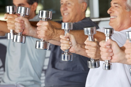 Many hands of senior people holding dumbbells in gym Stock Photo - 12954421