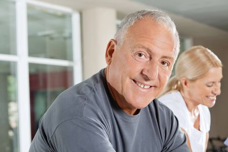 Portrait of a smiling senior man exercising in fitness center photo