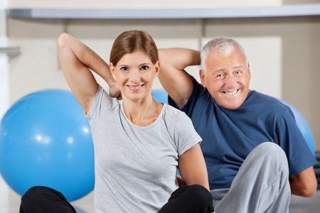 Elderly happy sport group doing back exercises in gym photo
