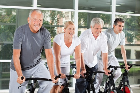 Happy senior people riding bikes together in fitness center photo