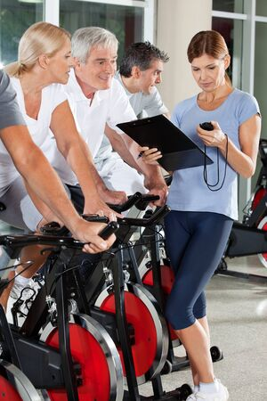 training programs: Fitness trainer coaching senior group in gym with stopwatch