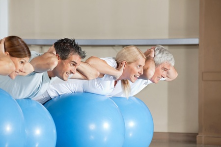 crunches: Senior people doing crunches on gym balls in fitness center Stock Photo