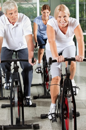 Senior people doing rehab fitness in gym on spinning bikes photo