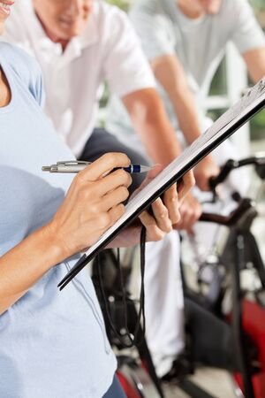 health club: Fitness trainer with checklist on clipboard in gym Stock Photo
