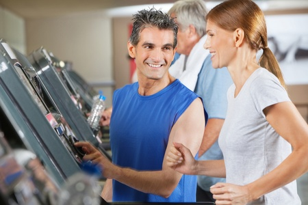 Fitness trainer explaining treadmill to jogging woman in gym photo