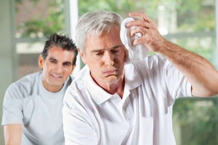 Senior man wiping sweat of his forehead with towel in gym photo