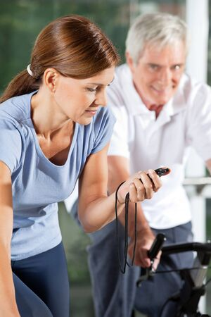 Woman in fitness center stopping time with stopwatch photo