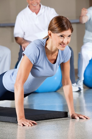 Woman in fitness center doing push ups on gym mat Stock Photo - 12954455