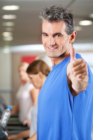 Man on treadmill holding his thumbs in up in gym photo
