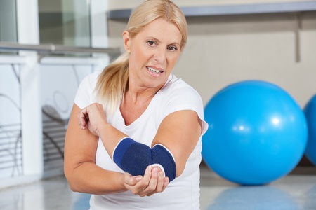 elbows: Elderly woman holding her aching elbow with bandage in gym Stock Photo