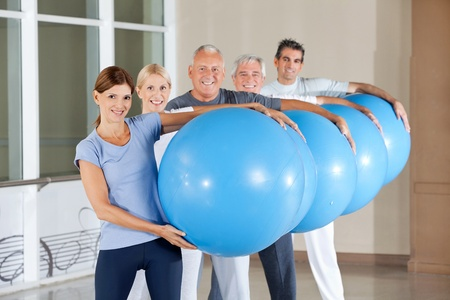Senior group carrying blue gym balls in fitness center photo