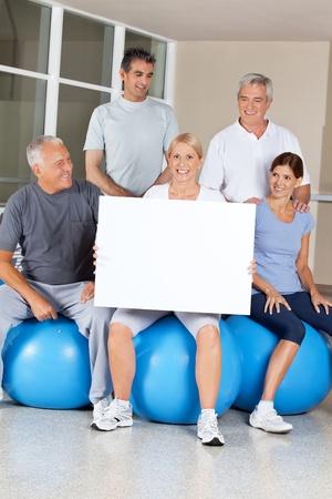 Senior citizens on gym balls doing advertising for fitness center Stock Photo - 12955914