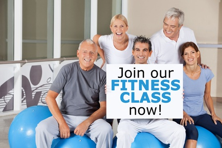 Happy senior group holding a Join our fitness class now sign photo