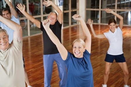 Feliz macho y hembra adultos mayores que bailan a la música en el gimnasio
