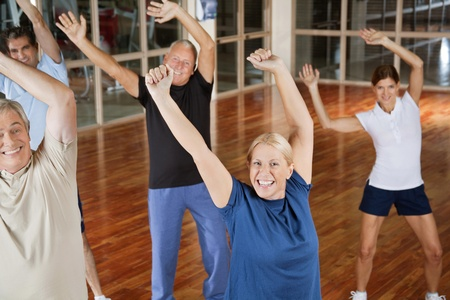 Happy male and female seniors dancing to music in gym photo