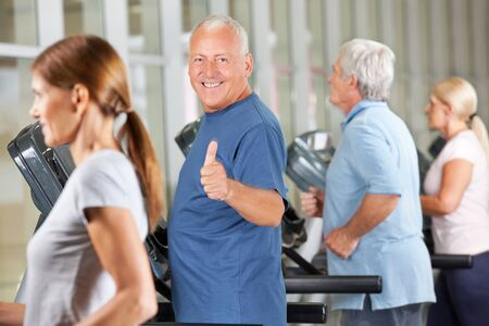 Happy senior man holding thumbs up on treadmill in gym photo