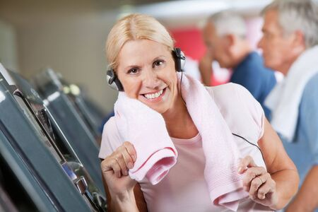 Happy active senior woman with headphones in fitness center photo