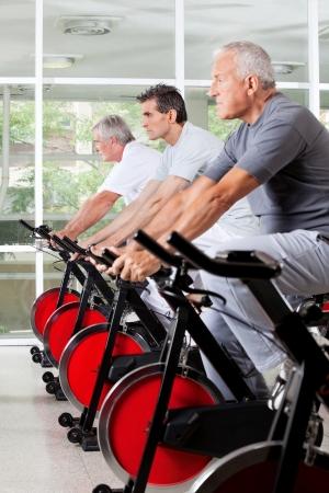 hombres haciendo ejercicio: Tres hombres mayores ejercen sobre bicicletas de spinning en el gimnasio