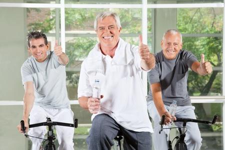 fitness hombres: Tres ancianos �xito la celebraci�n de los pulgares para arriba en las bicis en el gimnasio