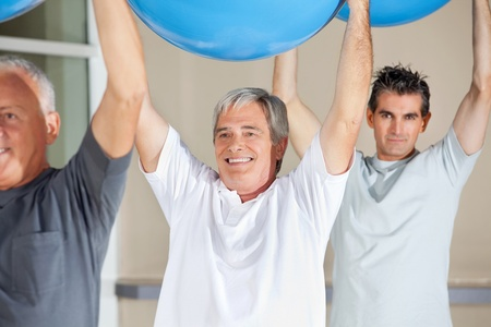 Senior citizens doing back exercises with gym balls in fitness center photo