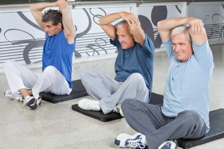 Elderly men stretching in fitness center on gym mats photo