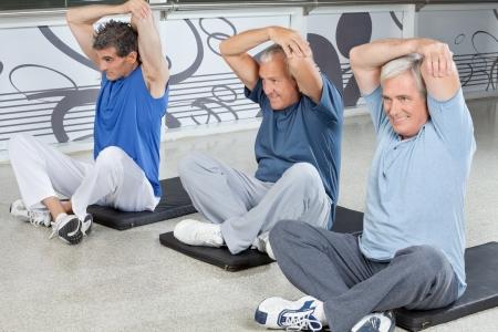 gimnasia aerobica: Hombres de edad avanzada que se extienden en el gimnasio en colchonetas de gimnasia