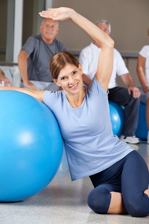 muscle formation: Smiling woman doing back exercises with gym ball in fitness center