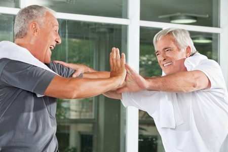 hale: Two cheering happy elderly man in fitness center giving High Five handshake