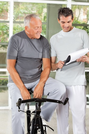 recommendation: Fitness coach explaining training plan to senior man in gym